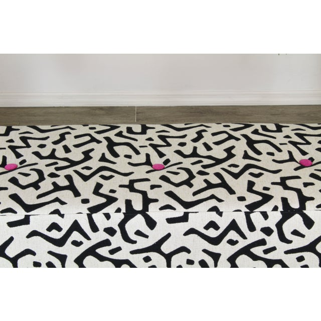 This bench is upholstered in a black and white abstract linen textile accented with fuchsia bottoms and piping and...
