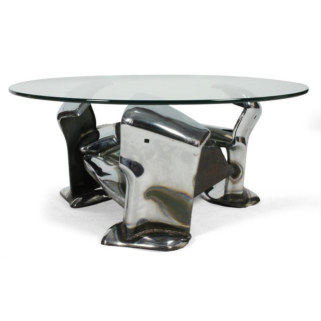 A unique cocktail table comprised of chromium plated steel car bumpers manipulated into a wreckage of twisted metal with...