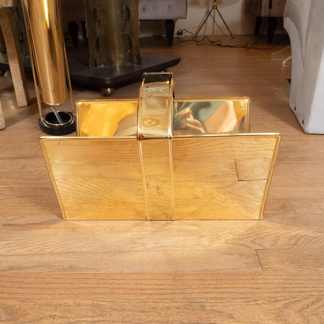 Whimsical brass magazine rack with buckle detail.