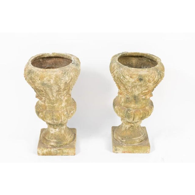 Pair of terracotta covered garden urns with green moss colored finish. The base measures 9.5 inches.