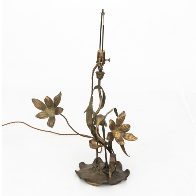 Circa 1910 Brass lamp featuring a crane and flower base. Recently rewired with new shade.