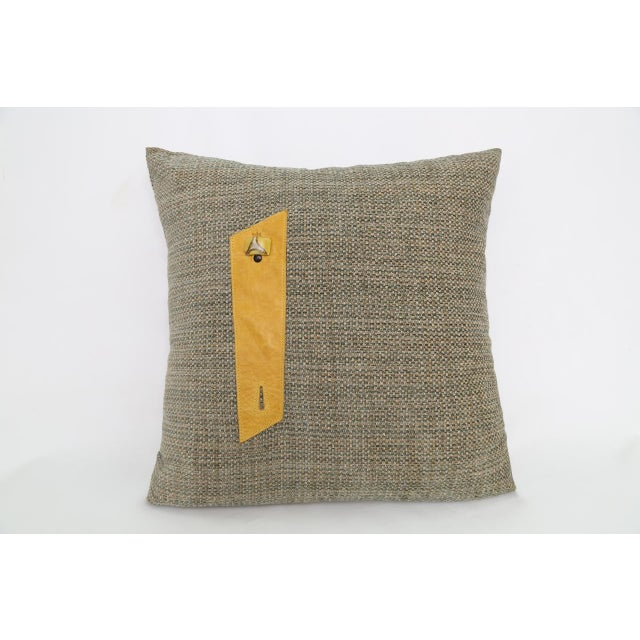 Pillow in original design. Gray burlap style fabric pillow with yellow leather belt.