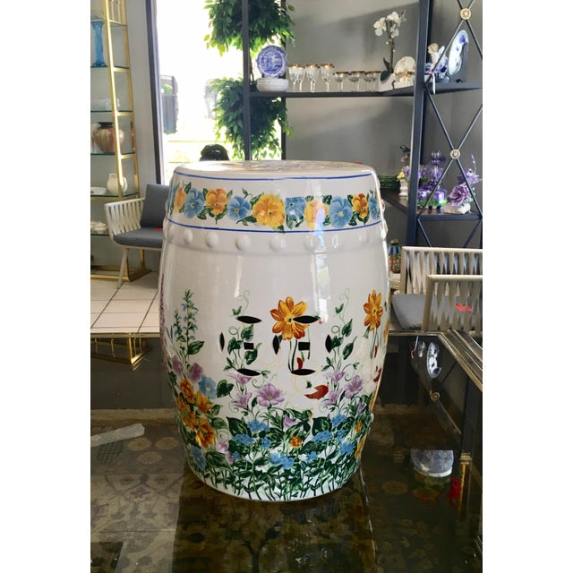 Chinoiserie style garden seat with vibrant depictions of flowers. Design on both sides and top consisting of cut out pieces.