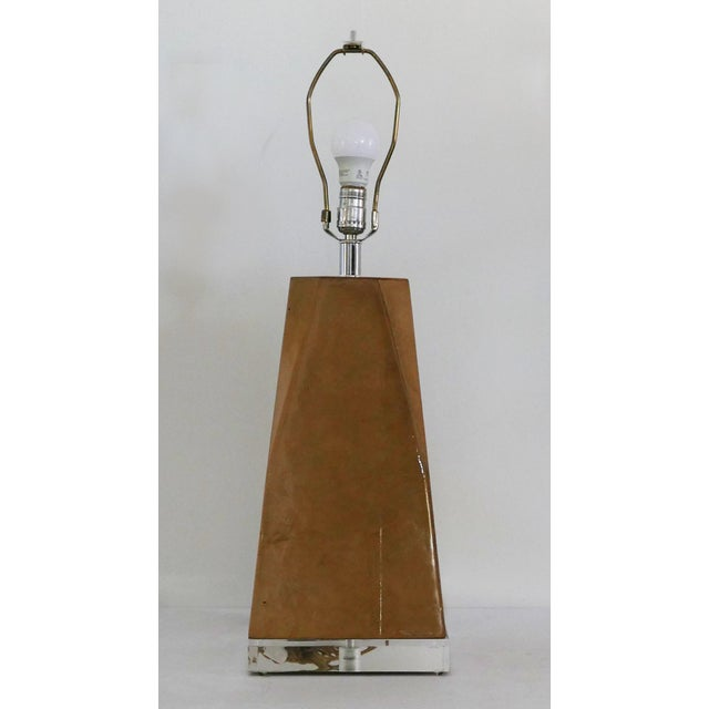 The lamp is lacquered goat skin lamp in the style of Karl Springer. It has a lucite base as well as finial. Lamp is a...