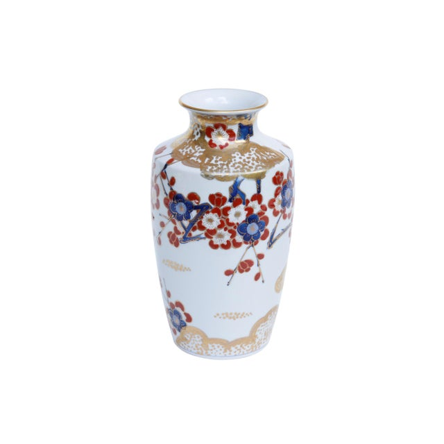 A hand painted Japanese porcelain vase. Decorated with beautiful bold florals in red, blue and gold. An angular shoulder...