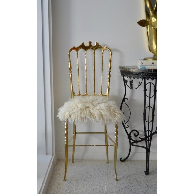 Stunning pair of Mid-Century brass side chairs, c. 1950s. These striking hall chairs are newly reupholstered in plush...