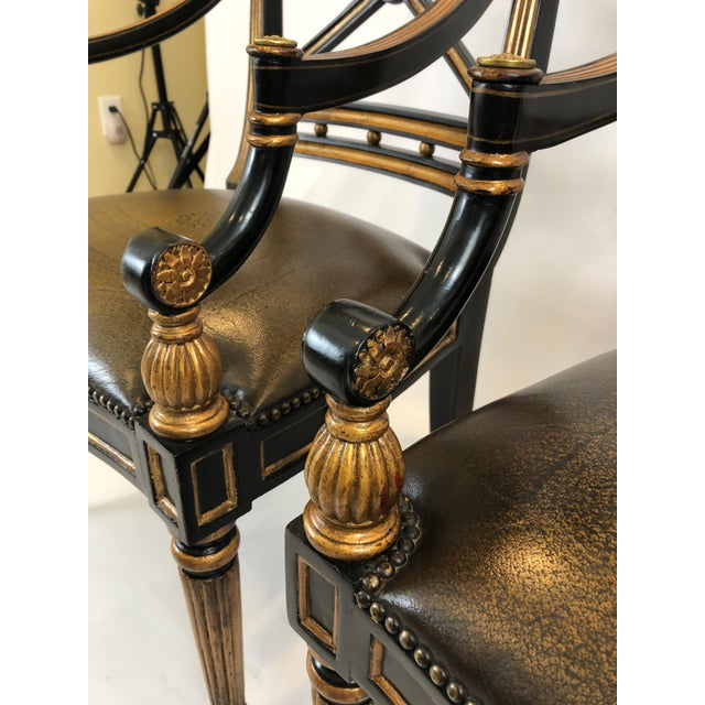Glamorous pair of Regency style black and gold armchairs having wonderful X-Style backs, gilded decorations including...