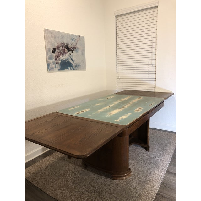 A one of a kind, robust, versatile, solid oak dining table with great original details, a newly updated distressed patina...