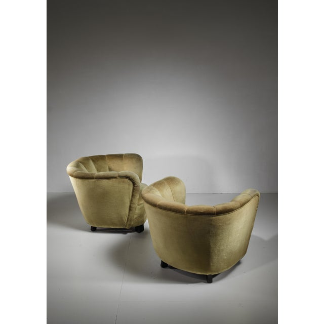 A pair of round Danish club chairs with a green velour upholstery. The chairs are in a very good condition with minor wear...