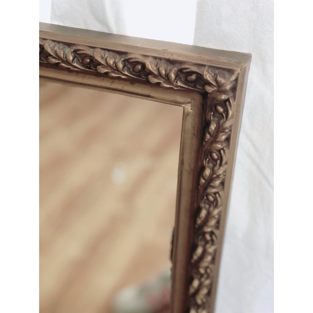 Elegant gilded wall mirror in a wood frame with base relief design. Natural age and distressing add to its charm.