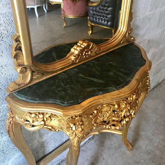 French Louis XVI console with mirror. The items were handmade massive wood and finished with gold leaf. It has a forrest...