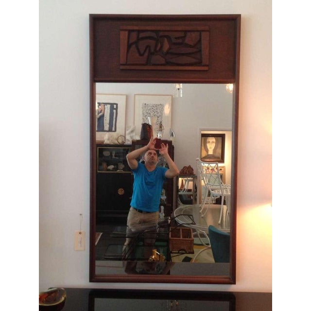 Chunky carved wood design accent on this mahogany framed mirror.