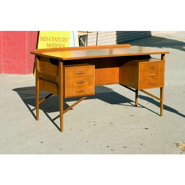 Large Danish teak desk in the style of Kai Kristiansen with floating drawers and table top. The desk features six side...