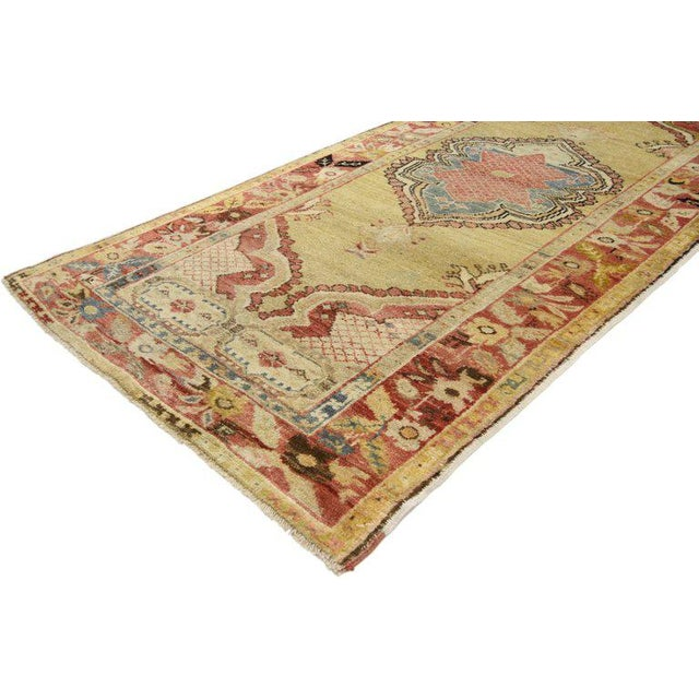Immersed in Anatolian history and time-softened colors, this hand knotted wool vintage Oushak rug combines simplicity with...