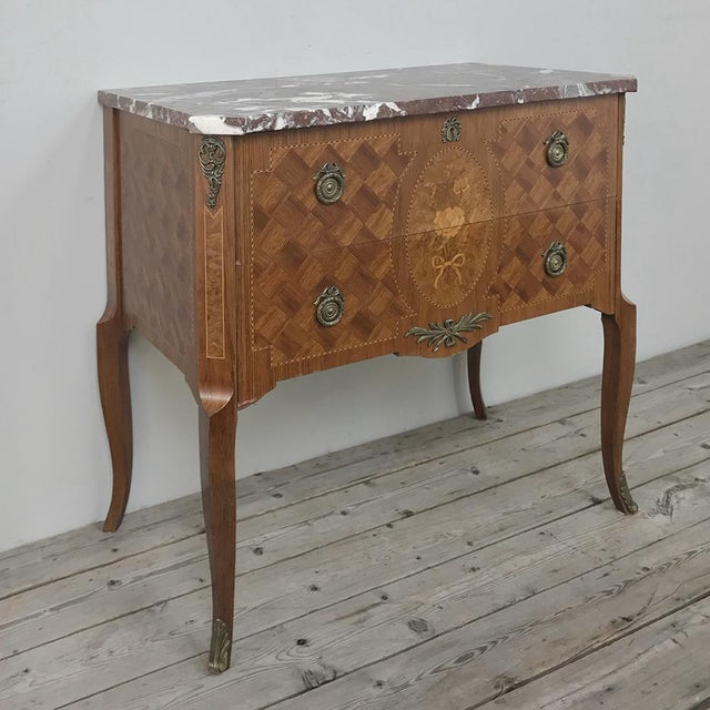 Antique French Louis XVI Marquetry Marble Top Commode combines the talents of an expert cabinet maker able to create the...