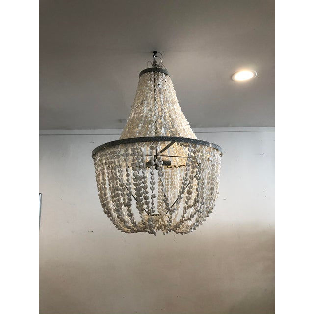 This is a classic, romantic empire style chandelier made with draping strands of pure white shells and a silver metal...