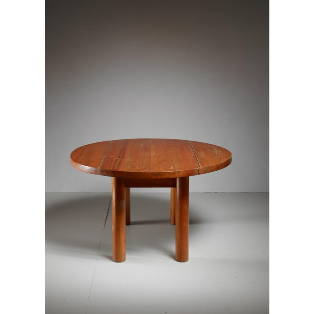 A unique pine drop-leaf dining table. This table was designed by Charlotte Perriand for the chalet-hotel Le Doron in the...
