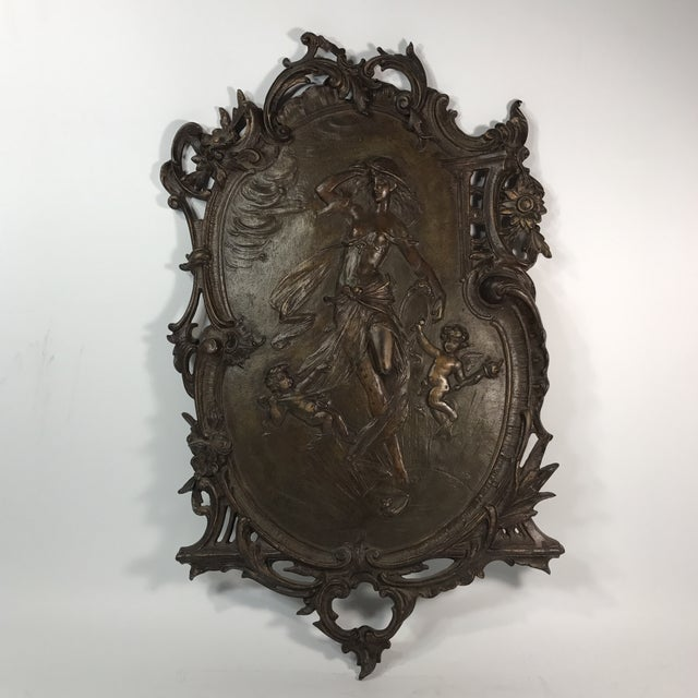 An antique gilded bronze wall hanging plaque featuring a gorgeous lady in the middle with two cherubs at her feet finished...