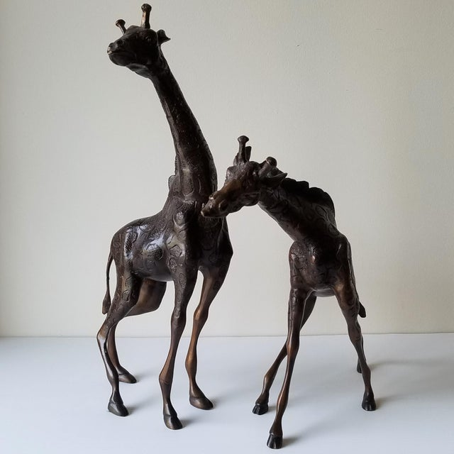 A pair of cast iron giraffes made by Metropolitan Galleries. These sculptures are smaller versions of the large giraffes...