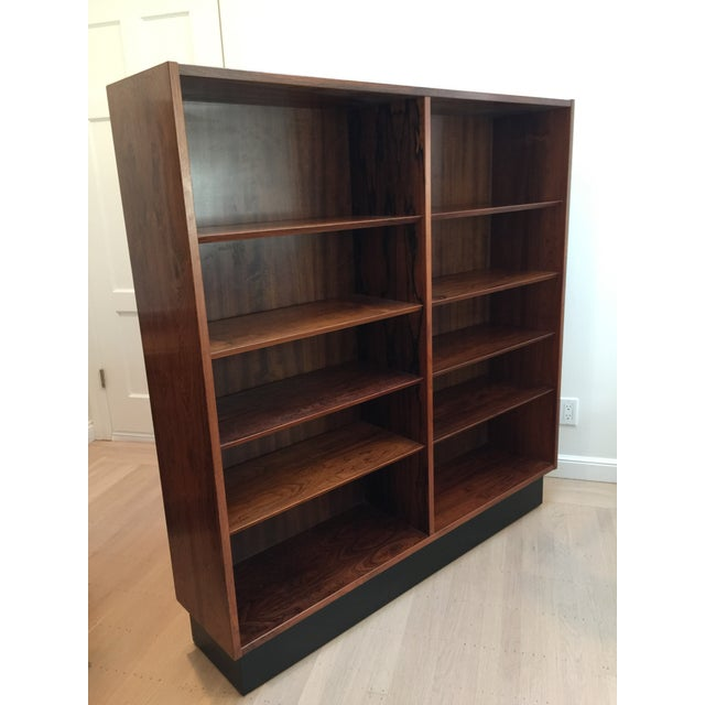 Danish modern rosewood bookcase with black base in the style of Arne Vodder. The height of all of the shelves can be...