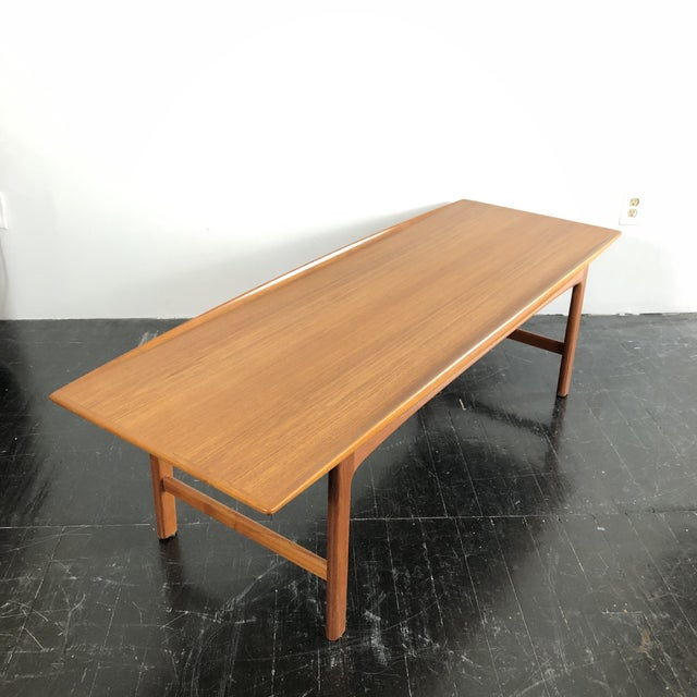1960s modern mid century teak coffee table by Folke Olsson and made in Sweden by Tingstromb. Elegantly curved raised edge...