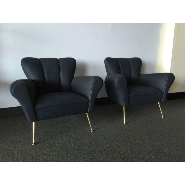 Definitely not black, these deep blue leather chairs are in a matte finish. The original brass legs with feet are solid....