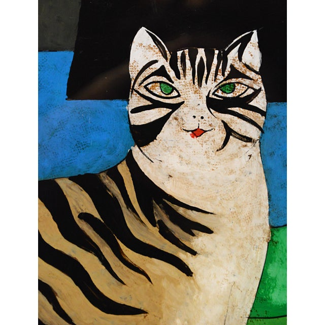 Early 20th century Spanish Folk art painting, reverse painted on glass, depicting a green-eyed striped kitty sitting on a...