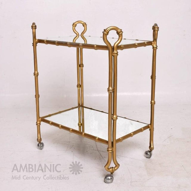 For your consideration a vintage service cart in faux bamboo (cast aluminum) in gold finish with new mirror shelves....