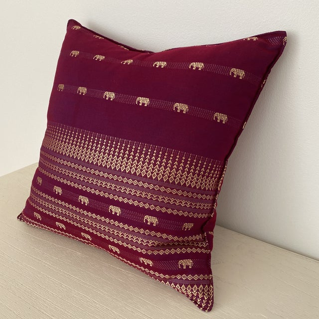 A beautiful magenta Thai silk pillow with elephant and geometric motif design. 100% silk. Zipper on the back side of the...