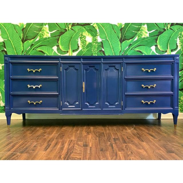 Mid-century dresser by American of Martinsville features brass hardware, brass feet, and assymetrical center doors...