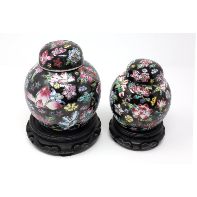 A vintage set of two hand-painted ceramic melon shaped ginger jars, with colorful flowers on a black background. Good...