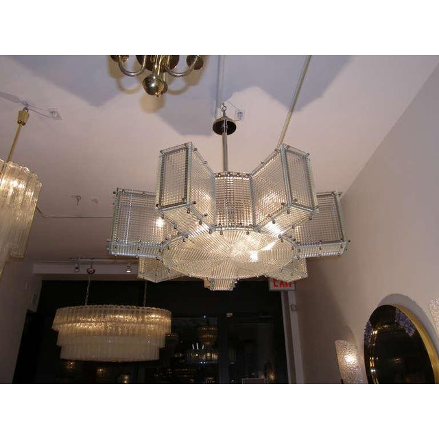 A large patterned glass chandelier with polished nickel frame and hardware by Craig Van Den Brulle.