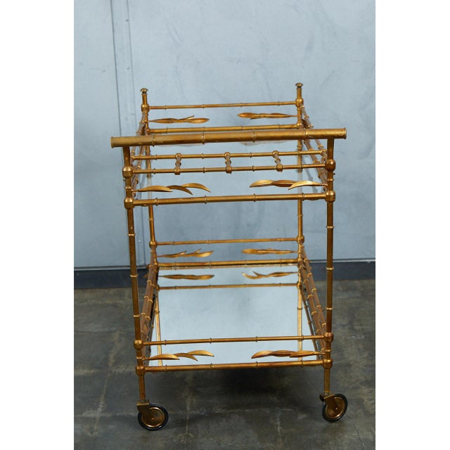 This faux bamboo drinks cart has decorative articulated leaves at each corner. The top shelf is glass and the bottom shelf...