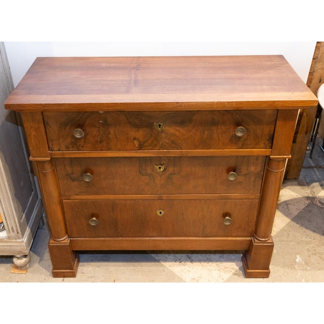 This late 19th century or early 20th century Empire commode is likely walnut and features three drawers with cast brass...
