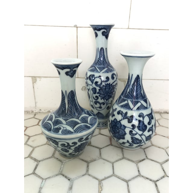 A set of three small Chinese vases with floral blue-and-white transfer pattern. Artist stamp on underside. Measurement is...