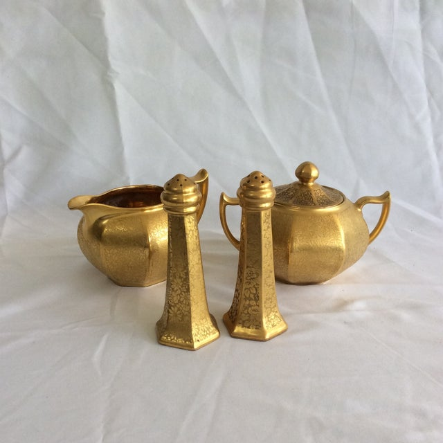 Antique set consists of a pair of salt and pepper shakers, creamer, and a sugar bowl. Beautiful floral embossing in 22k...