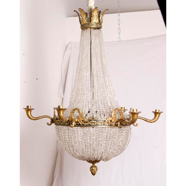 A very elegant and large beaded crystal chandelier with ormolu mounts done in the Empire style. Featuring swags of laurel...