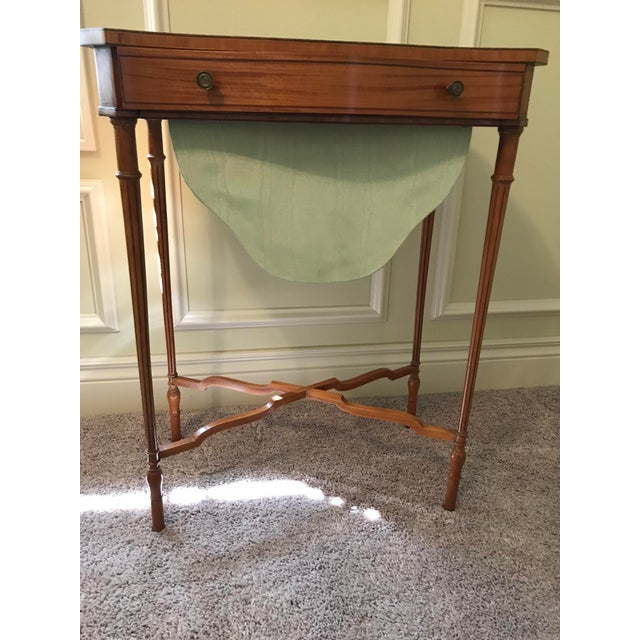 This English Edwardian satinwood sewing table was manufactured in the Sheraton style (1810 or so), which is about 100...