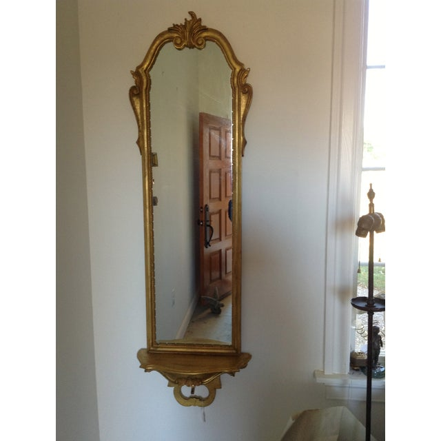 A 1950s Italian Rococo-style mirror with a scalloped shelf bracket. This piece is in excellent vintage condition, with one...