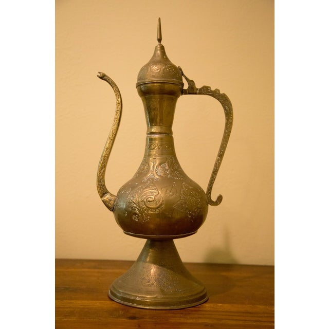 Old Moroccan tea pot made of solid brass with detailing throughout body, handle, and spout. Very substantial piece in very...
