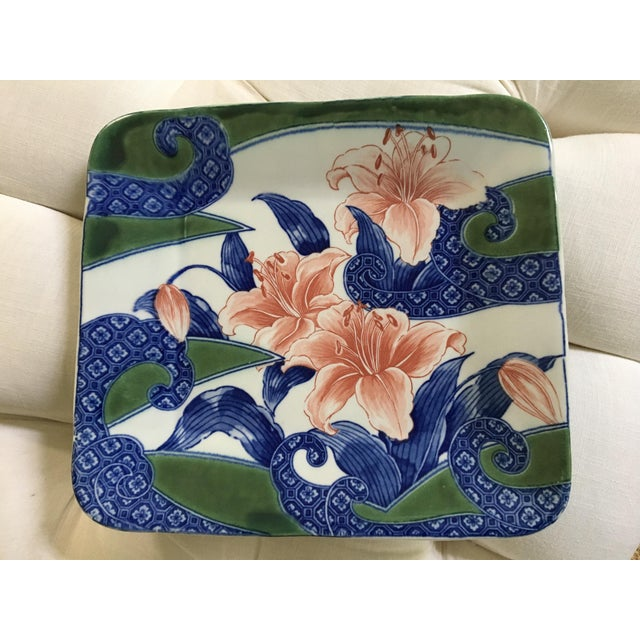 A beautiful serving or decorative porcelain platter with a floral motif and Asian flair. This is a square platter with...