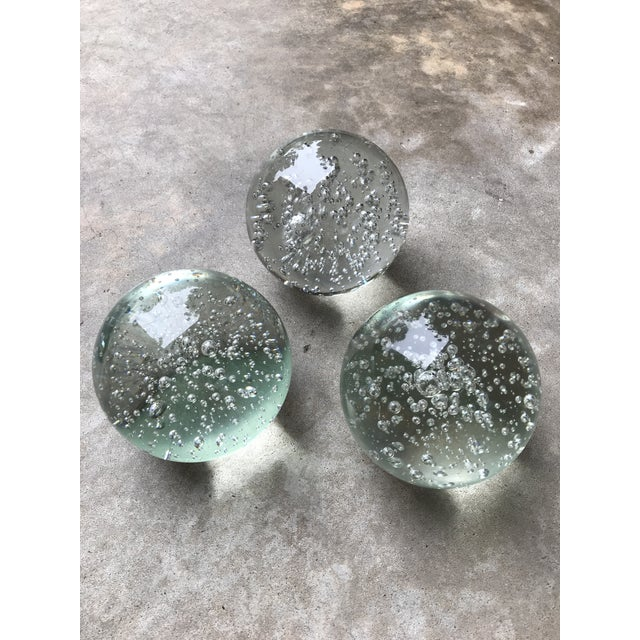 Offered is a trio of Glass spheres, sold as a set. They have beautiful bubbles suspended in the glass. One of the balls...