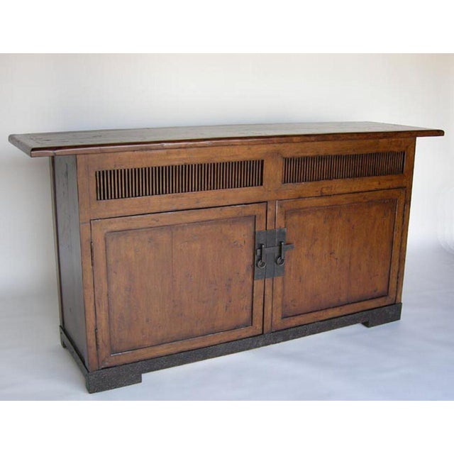 Japanese style media console with slatted panels, interior shelf and custom-made hand, forged iron hardware and base. Can...