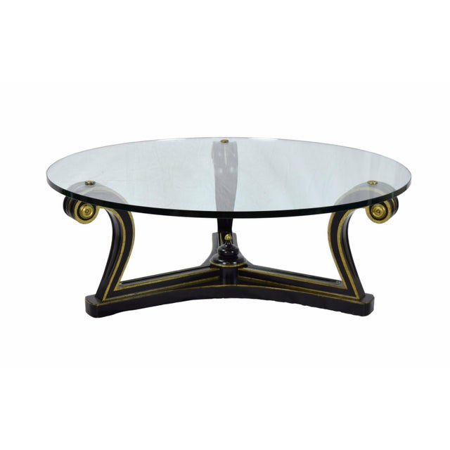 Gorgeous vintage Empire inspired coffee table made of gilt ebonized wood with a round thick glass top supported by three...