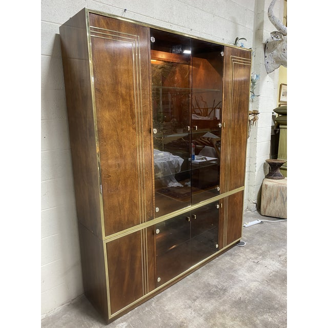 This is a fantastic piece. Faux grain wood panels with brass accents. Mirrored back wall, lighted and tons of storage. The...