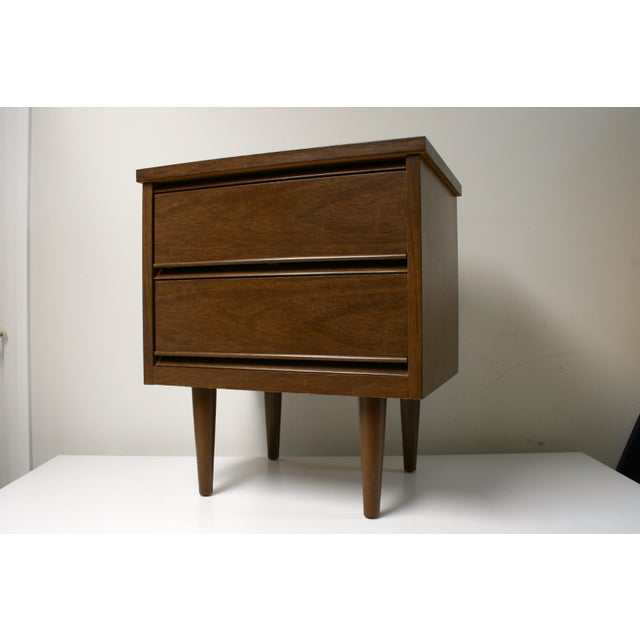 Classic mid century modern nightstand with two drawers. Small blue mark on top corner and small nick on side.