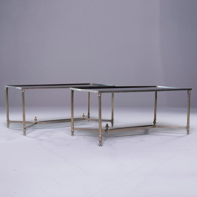 Pair circa 1940s pair of French neoclassical cocktail tables feature silver tone metal frames with reeded legs and...