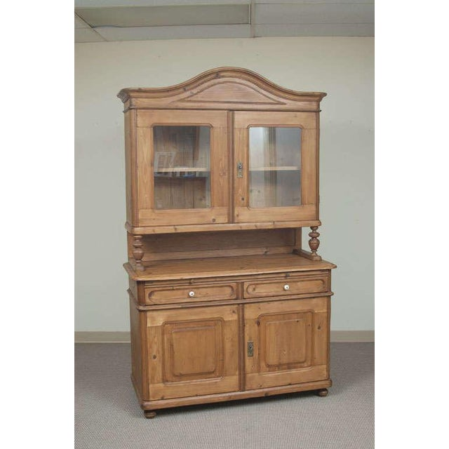 A very handsome Baroque-style glazed dresser featuring a bonnet-topped upper section with two glazed wide-swinging doors...