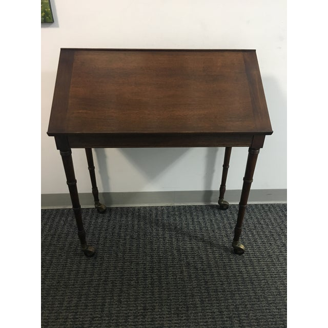 This beautiful wood table features a faux bamboo detailing on the legs, brass wheels, and a unique tilt-top. Use as a...