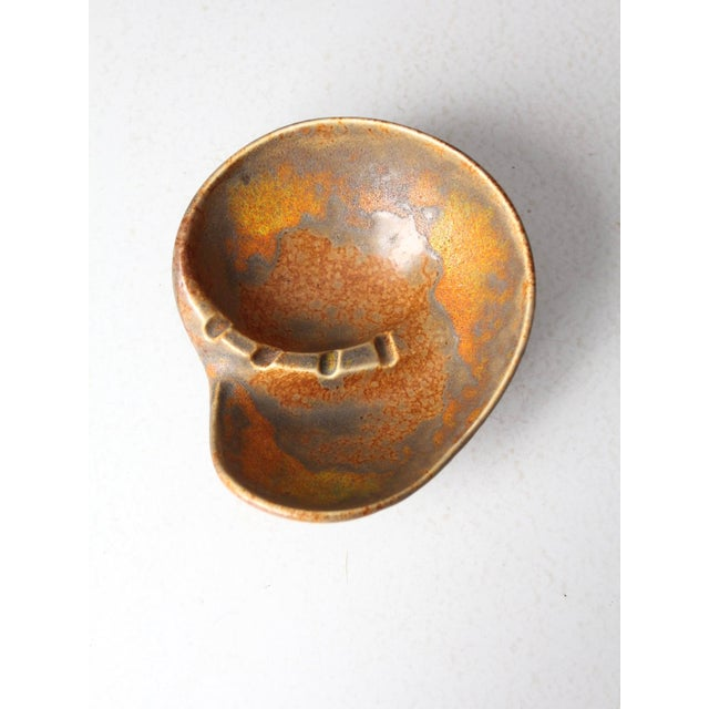 This is a mid-century Haeger pottery ashtray. Sleek, dynamic lines shape the large ashtray with a striking orange lava...